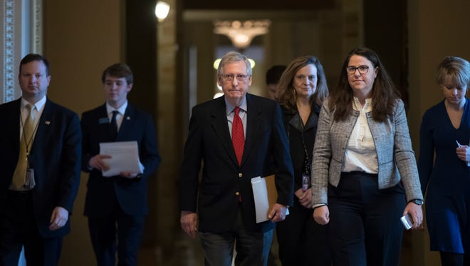 Senate Majority Leader Mitch McConnell, R-Ky., walks to the chamber on the first morning of a government shutdown Saturday, Jan. 20, 2018.