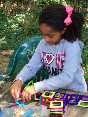 Mia Chatman, 7, plays at one of the stations on the quarter mile Woodland Elves Trail, which winds around the wooded yard of Williamson's residential home.