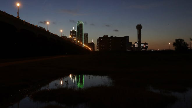 Reunion tower, right, stands with the lights out as the sun rises over downtown Dallas, Friday, July 8, 2016. Many Dallas business turned out their lights to honor the police killed and wounded in an attack Thursday evening. (AP Photo/Eric Gay)