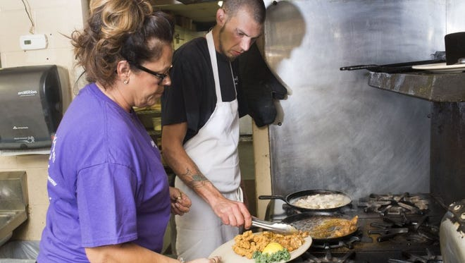 Co-owner Cindy Cantillo holds a plate for cook Shane Freeman as he serves up alligator entrées in honor of the Tennessee-Florida football game on Thursday, Sept. 22, 2016, at Bayou Bay Seafood House in South Knoxville. The gator is preparing three ways — grilled, blackened, and fried.
