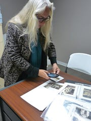 Dr. Paula Summerly examines the Bowie Historical Committee's collection of Bowie family memorabilia at the Bowie Museum inside the Bowie Nature Center in Fairview.