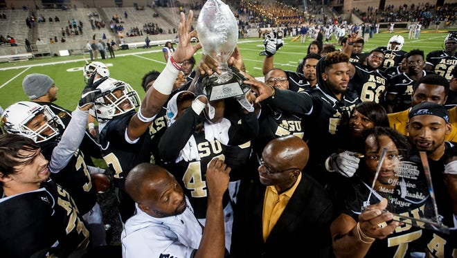 Alabama State players lift the Turkey Day Classic trophy after defeating Miles College at ASU Stadium in Montgomery, Ala. on Thursday November 24, 2016.