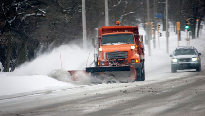 A plow clears snow from the 4500 block of South Lake Drive Wednesday, Jan. 1, 2013, in Cudahy.