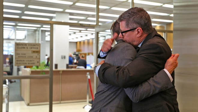 """Rob MacPherson, left, and Steven Stolen, who are married, say goodbye to each other after visiting Marion County Clerk Beth White to thank her for her support, at the Marion County Clerk's office in the City/County building, Monday, October 6, 2014.  The U.S. Supreme Court denied requests to take up the same-sex marriage issue, meaning gay marriage is legal in Indiana. MacPherson and Stolen were plaintiffs in the ACLU case, """"So we won today,"""" they said."""