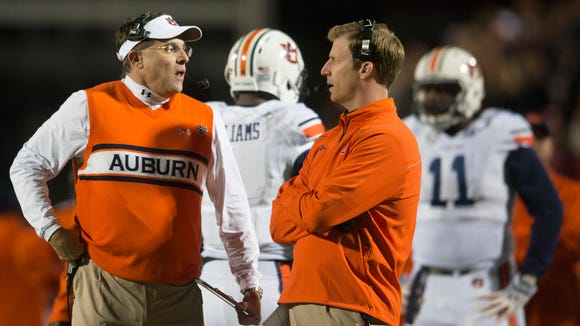 Auburn head coach Gus Malzahn speaks to offensive coordinator Rhett Lashlee during the NCAA football game at University of Mississippi in Oxford, Miss., on Saturday, Nov. 1, 2014. Auburn defeated Mississippi 35-31.