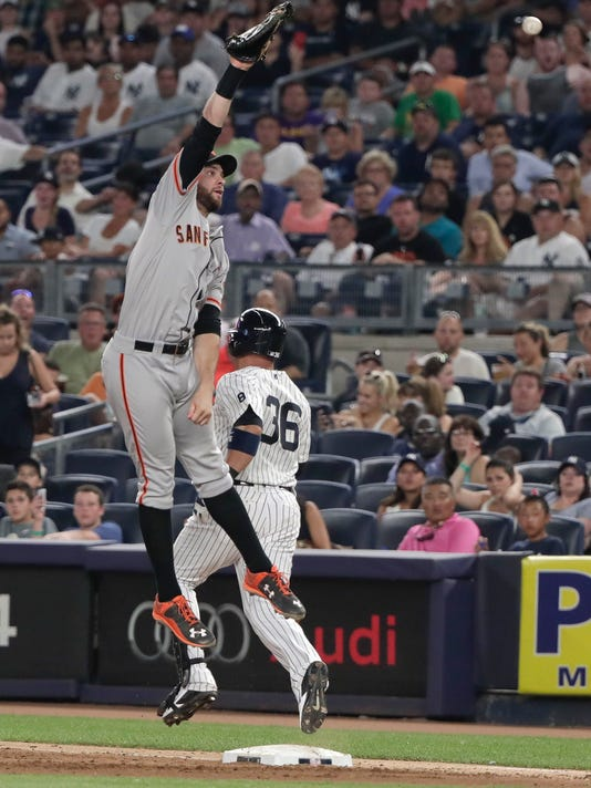 New York Yankees' Carlos Beltran (36) reaches first base safely on a throwing error by San Francisco Giants shortstop Brandon Crawford to first baseman Brandon Belt during the seventh inning of a baseball game, Friday, July 22, 2016, in New York. The Yankees won 3-2. (AP Photo/Julie Jacobson)