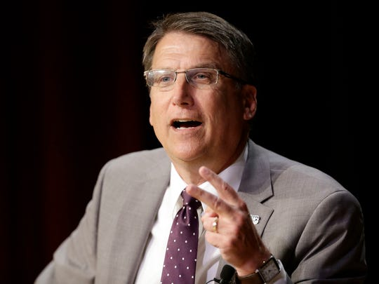 """In this May 4, 2016 file photo, North Carolina Gov. Pat McCrory make remarks concerning House Bill 2 while speaking during a government affairs conference in Raleigh, N.C. Shortly after he signed the law, Republican then-Gov. Pat McCrory issued a statement assuring residents it wouldn't affect North Carolina's status as """"one of the top states to do business in the country."""" The Associated Press has determined that North Carolina's HB2 law will cost the state more than $3 billion in lost business over a dozen years. (AP Photo/Gerry Broome, File)"""