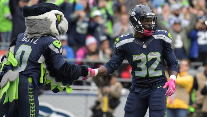 Seahawks running back Christine Michael (32) shakes hands with mascot Blitz after scoring on a 1-yard touchdown in the fourth quarter.