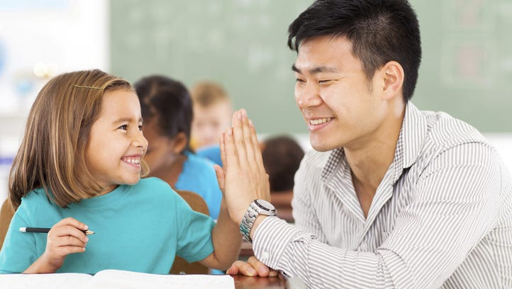 A teacher and a student high-five.