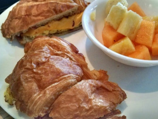 Frank's Deli & Cafe's bacon egg and cheese croissant sandwich with a side of cantaloupe and pineapple.