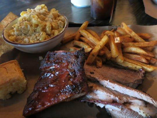 Tender, mildly smoked slices of beef brisket, shown with an optional quarter-slab of glazed ribs, are served here with seasoned fries and mac-and-cheese at Yardbird Smoked Meats in Keego Harbor.