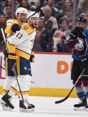 Nashville Predators center Nick Bonino (13) celebrates his goal with defenseman Roman Josi (59) while Colorado Avalanche defenseman Tyson Barrie (4) reacts during the second period of game 6 in the first round NHL Stanley Cup Playoffs at Pepsi Center, Sunday, April 22, 2018, in Denver, Colo.