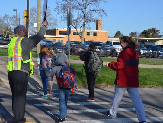 Merle Boyer gets a high-five from a Riverside Elementary