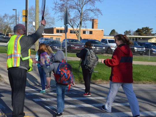 Merle Boyer gets a high-five from a Riverside Elementary student on his first day back to work as a crossing guard on Monday, April 30, 2018.