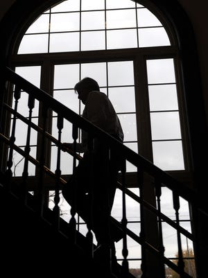 Richard Otto climbs the 30 steps inside Weldon Huston & Keyser Tuesday afternoon during a tour of the the building.  Most of the woodwork, including the staircase railing, still remains since the building's construction in 1912.