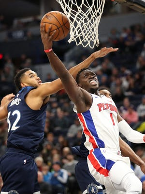 Pistons guard Reggie Jackson shoots as Timberwolves center Karl-Anthony Towns defends during the second half Nov. 19, 2017 in Minneapolis.