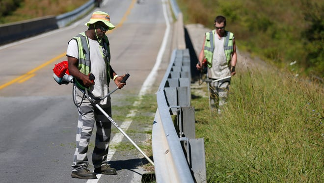 Greene County Jail inmate James Dokes uses a weed eater on Farm Road 115 to clear brush from around a guardrails on Tuesday, Sept. 27, 2016. Dokes is park of the Greene County Inmate Labor Initiative, a volunteer program for inmates to do the landscaping around the Greene County Justice Center, pick up trash along roadways and clean up after public events.