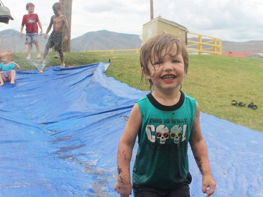 Ivan Moreau, 3 years old, cleans off on the slip and slide.