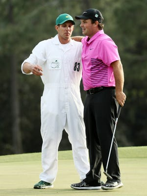 Patrick Reed of the United States celebrates with caddie Kessler Karain after making par on the18th green during the final round to win the 2018 Masters tournament at Augusta National Golf Club on April 8.