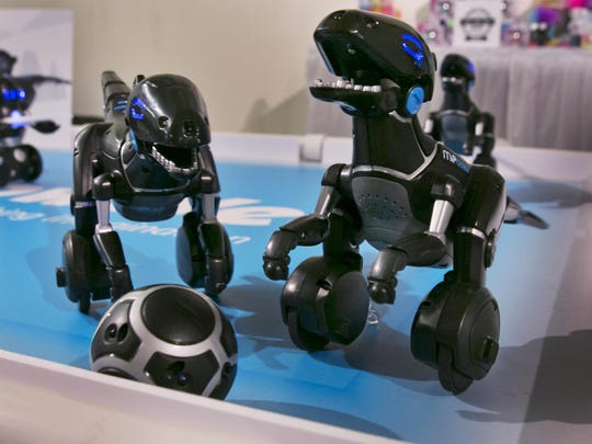 The MiPosaur, from Wowwee, go through their paces. The mini robots can chase after a matching ball, go for a walk with its owner and even dance and make happy sounds.