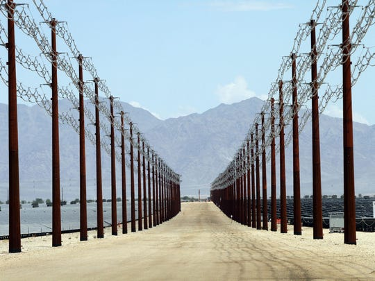 Overhead transmission lines funnel power underground to a nearby substation at the 550-megawatt Desert Sunlight solar farm in Desert Center, California, about an hour east of the Coachella Valley, on Aug. 20, 2014.