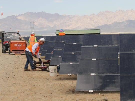 Workers install and connect solar panels at the 550-megawatt Desert Sunlight solar farm in the California desert, about halfway between the Coachella Valley and the Arizona border, on Aug. 20, 2014.