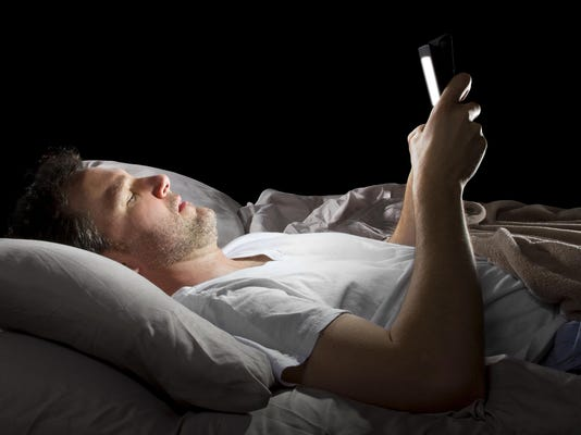 Male in bed browsing the internet late with a tablet