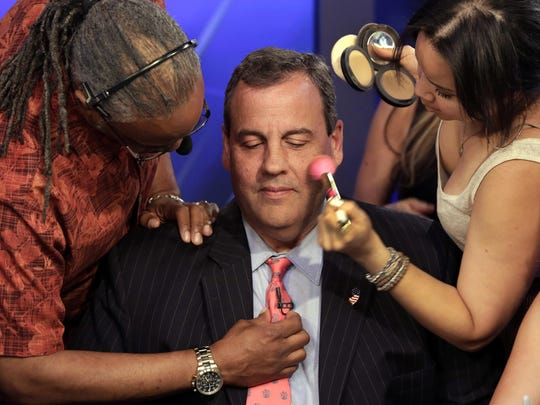 Gov. Chris Christie gets his microphone and makeup for an appearance on the Fox News Channel in New York during his presidential run.
