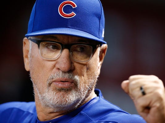 Chicago Cubs manager Joe Maddon gives a fist-bump in the dugout prior to a baseball game against the Arizona Diamondbacks, Sunday, Aug 13, 2017, in Phoenix. (AP Photo/Ross D. Franklin)