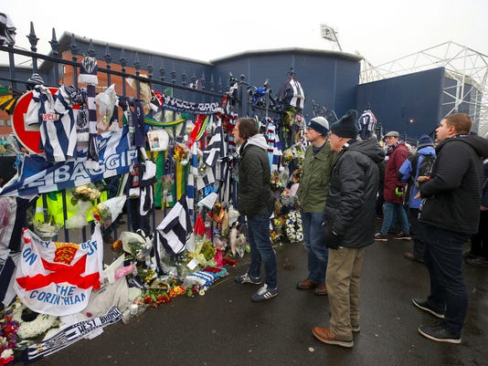 Fans look at tributes to late international soccer playerCyrille Regis ahead of the English Premier League soccer match at The Hawthorns, West Bromwich, England, Saturday Feb. 3, 2018.  Regis died Jan. 14, 2018. (Nick Potts/PA via AP)