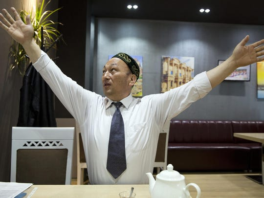 Omir Bekali demonstrates how he was strung up by his arms in Chinese detention before being sent to an internment camp, during an interview March 29 in Almaty, Kazakhstan.