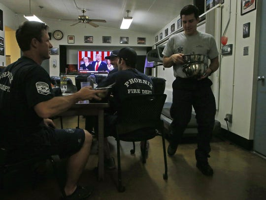 Firefighters clear away their dinner dishes as they all watch the State of the Union address by President Donald Trump inside their firehouse Tuesday, Feb. 5, 2019, in Phoenix.