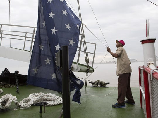 In this March 15, 2015 file photo, Dwayne McCornick, a deck hand on the Natchez steamboat for 16 years, raises the Union Jack naval flag on the Mississippi River in New Orleans.