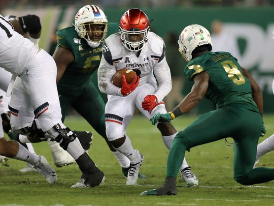 Cincinnati running back Michael Warren II tries to avoid a tackle by South Florida's Devin Studstill during the first half of an NCAA college football game, Saturday, Nov. 16, 2019, in Tampa, Fla. (AP Photo/Mike Carlson)