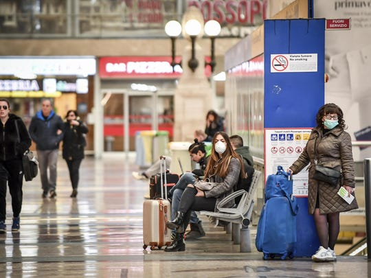 People wear masks as they wait inside Central train station, in Milan, Italy, Sunday, March 8, 2020. Italy announced a sweeping quarantine early Sunday for its northern regions, igniting travel chaos as it restricted the movements of a quarter of its population in a bid to halt the new coronavirus' relentless march across Europe. (Claudio Furlan/LaPresse via AP)