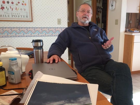Richard O'Connor sits in his Clancy home and discusses a photo, shown in the foreground, that one of his cameras has captured. He believes it is of a UFO.