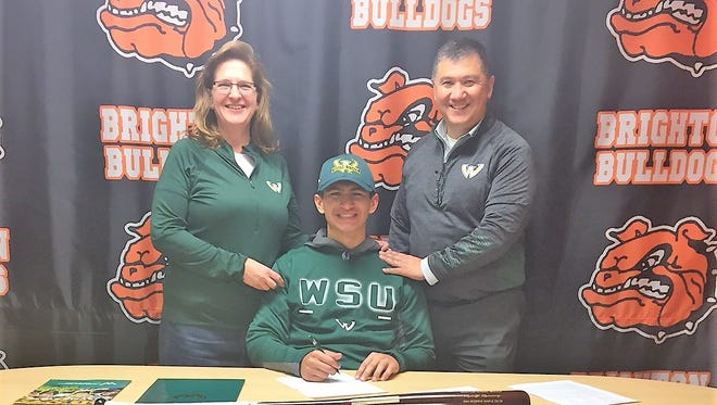 Brighton's Rudy Ramirez sits with his parents after signing on Thursday with Wayne State University for baseball.
