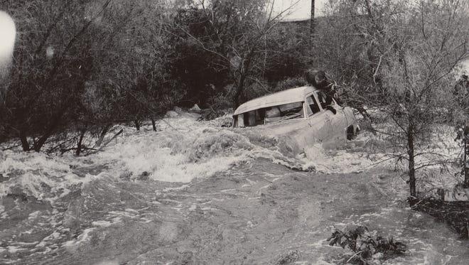 Man climbs atop his car as it succumbs to flooding Dec. 26, 1959.
