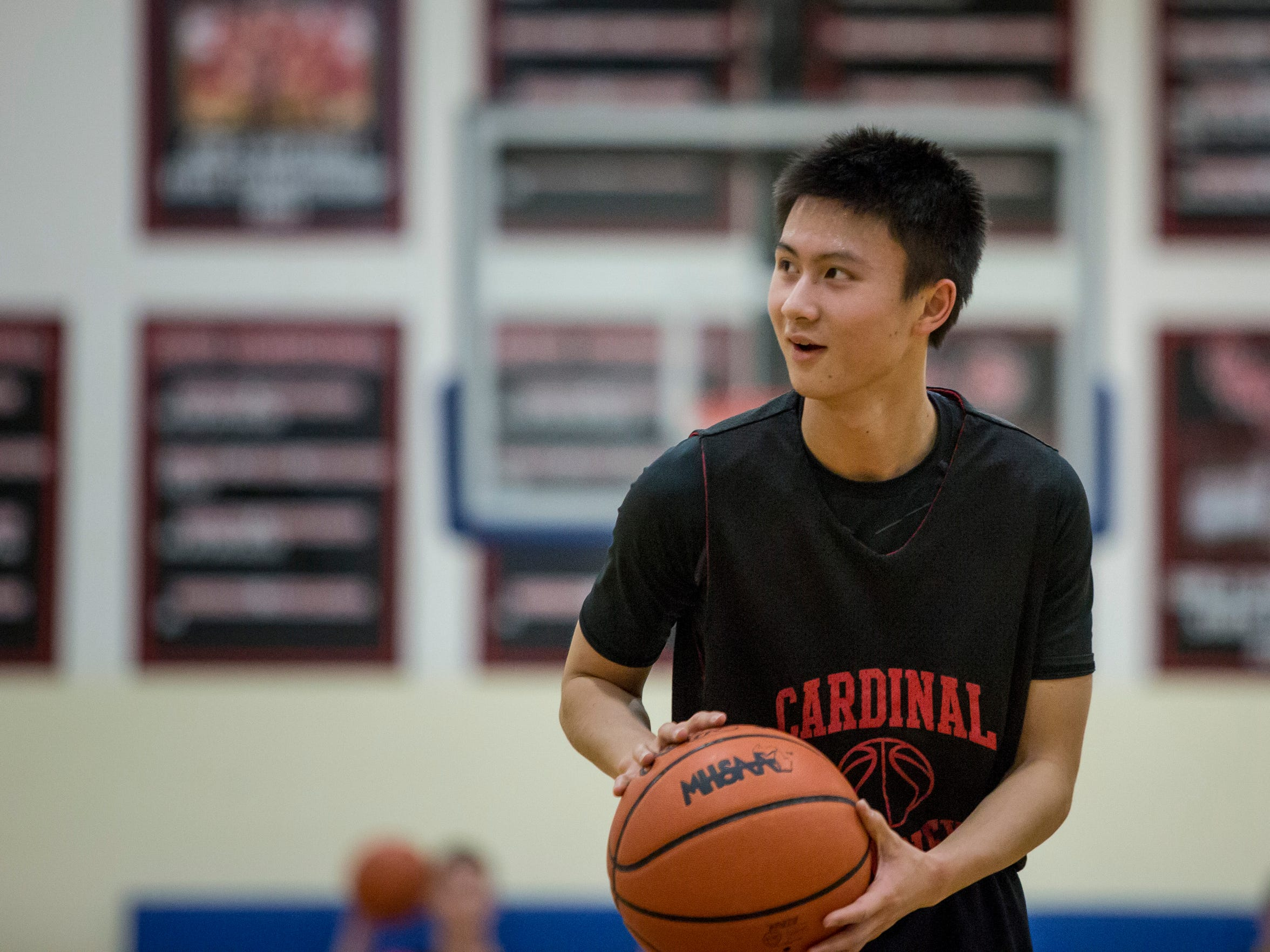 Senior Chris Xuan, 19, chats with teammates as he takes a shot during basketball practice Wednesday, Jan. 27, 2016 at Cardinal Mooney High School in Marine City. Xuan is an exchange student from Shenzhen, China.