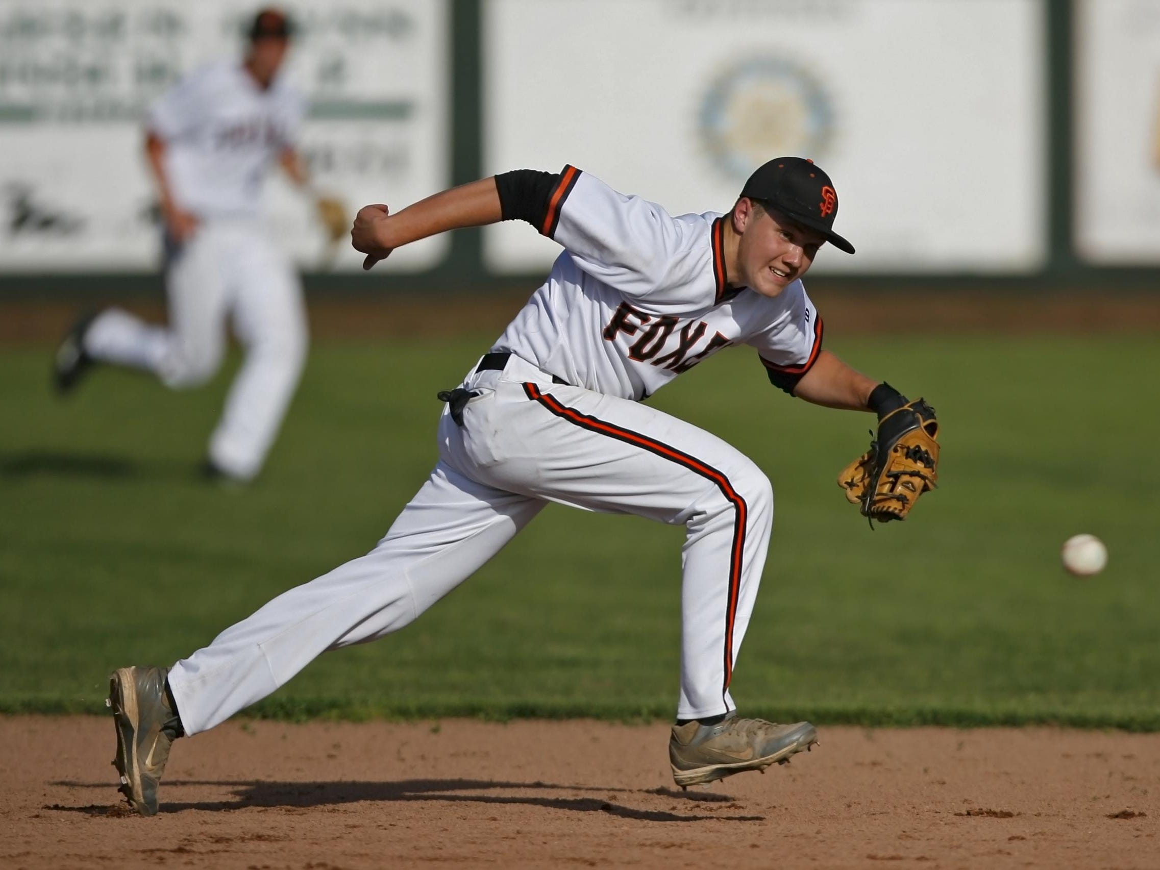 Silverton shortstop Grant Roth can't catch up with a ground ball up the middle in the top of the sixth inning of Silverton's 9-2 loss in a Mid-Willamette Conference baseball game, at Silverton, on Wednesday, Apr. 30, 2914.