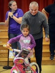 Jiselle Govea, 5, rides away on her new bike Wednesday, Jan. 4, 2017, during a Christmas gift distribution at Oak Park Elementary School. Martin De Los Santos of L&F Distributing, one of the event's sponsors, helps her get started.