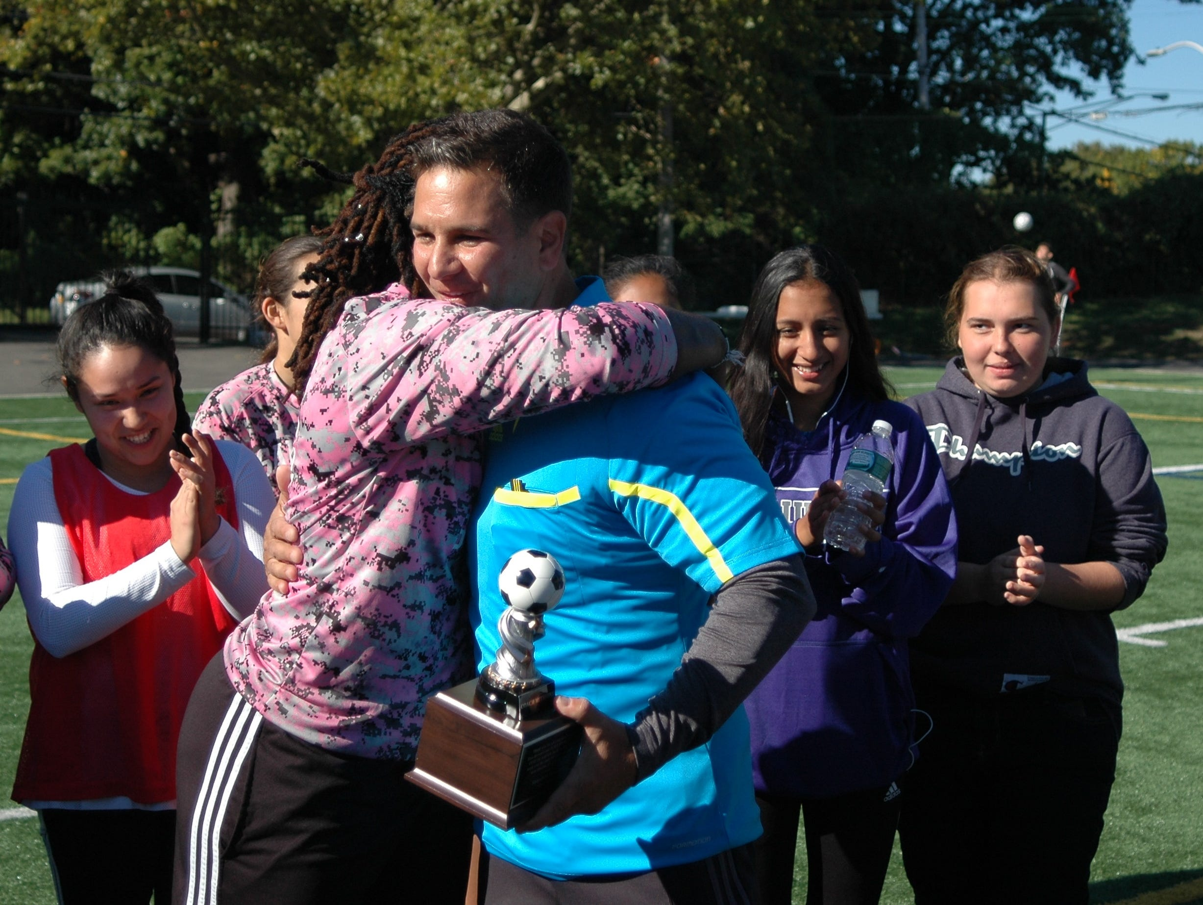 Saunders girls soccer head coach Carlo Mitrione receives a hug from former player Delmara Reece after being honored during the school's alumni game on Saturday, October 10, 2015. Mitrione, who has coached both boys and girls soccer at the school for 19 years, will be retiring from coaching at the end of the season.