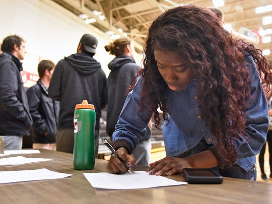 Students sign petitions Wednesday in Halenbeck Hall