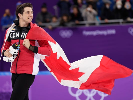 Canada's Scott Moir wears his national flag as he celebrates on the ice following his team's win in the figure skating team event in the Gangneung Ice Arena at the 2018 Winter Olympics in Gangneung, South Korea, Monday, Feb. 12, 2018. (AP Photo/Julie Jacobson)