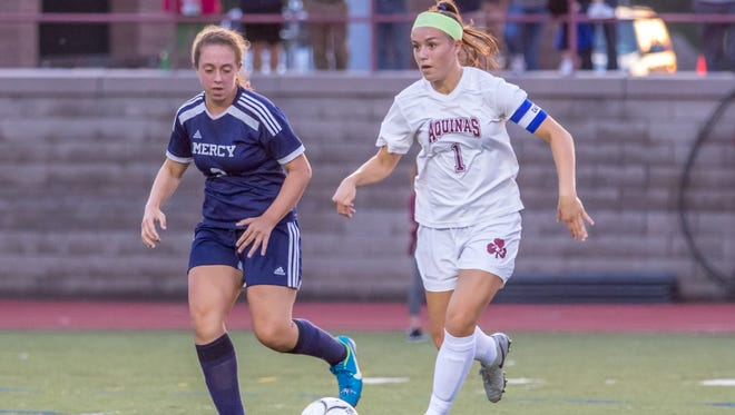 Alana Piano, right, in Aquinas' all-time leader in goals and points in girls soccer.