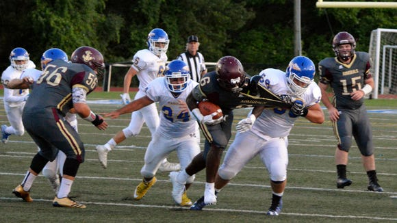 Arlington tailback Riccardo Yolas (6) is pulled down