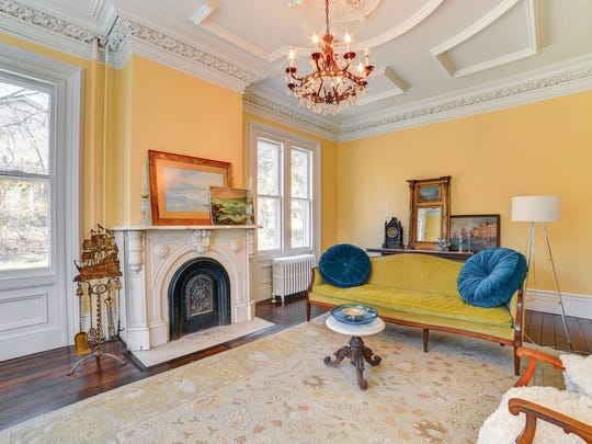 There are intricate crown moldings, brass hardware and soaring floor-to-ceiling windows,