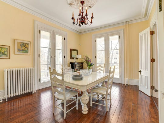 Note the intricate crown moldings, brass hardware and soaring floor-to-ceiling windows.