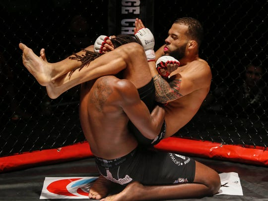 Jordan Young, right, a MMA fighter from Des Moines, works to administer a submission hold against Jaquis Williams of Omaha, Neb., in their middleweight championship fight during the Midwest Cage Championships Thanksgiving Throwdown on Wednesday, Nov. 25, 2015, in Des Moines.