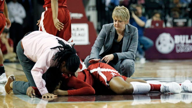 Alabama head coach Kristy Curry, right, and a team trainer check on the status of forward Ashley Williams, who was injured in a collision late in Sunday's game.